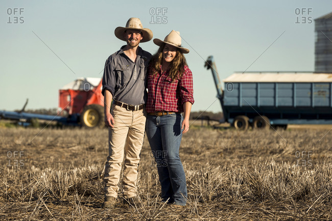 Young farmer couple standing in field while working