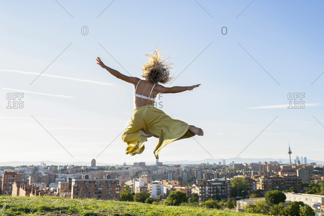 Back view full body barefoot female in bra and loose trousers jumping with arms raised while spending on grassy hilltop against city buildings