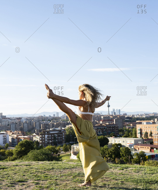 Back view slim flexible female in loose trousers performing Extended Hand To Big Toe pose while practicing yoga on sunny hilltop against urban environment