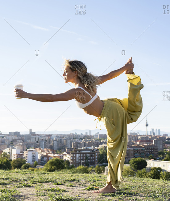 Side view full body barefoot female in bra and loose trousers performing Dancers Pose and outstretching hand with cup of coffee while practicing yoga on grassy hill against urban environment
