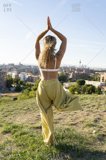 Back view full length fit female in white bra and loose trousers doing Tree Pose with hands together above head while standing on hilltop against city buildings