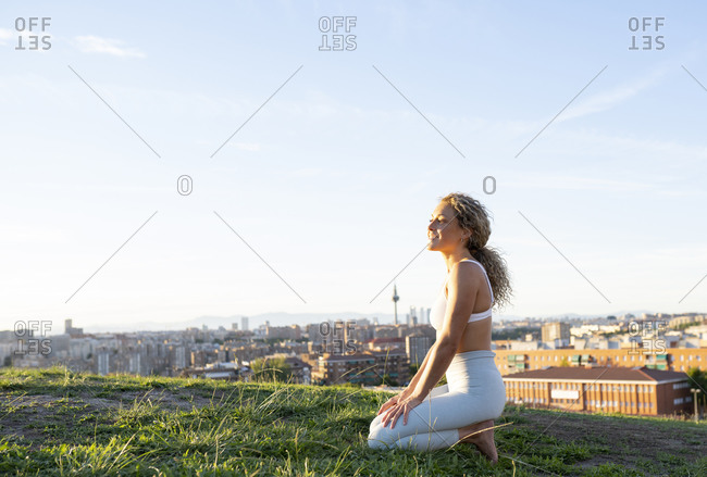 Side view full body sporty woman in legging and sports bra sitting on knees on grassy lawn and looking away with smile against contemporary city