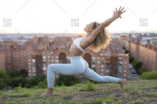 Side view full length concentrated female with perfect figure performing Low Lunge Pose with arms raised during yoga training on green crowded lawn