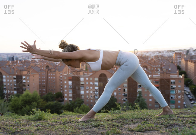 Side view full length barefoot female in leggings practicing yoga and bending down with arms outstretched against city buildings