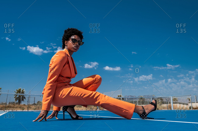 Side view of young stylish black woman in orange apparel with sunglasses and high heeled sandals squatting near fence on sports ground looking at camera