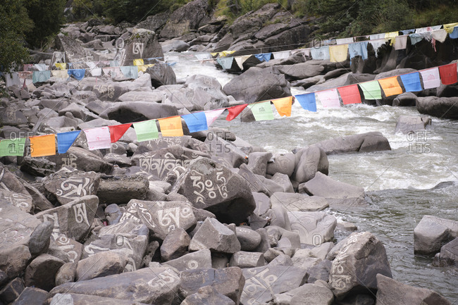 September 9, 2020: Sanskrit mantra Om Mani Padme Hum engraved on surface of big grey stones in mountain river in village of Baiyu in China