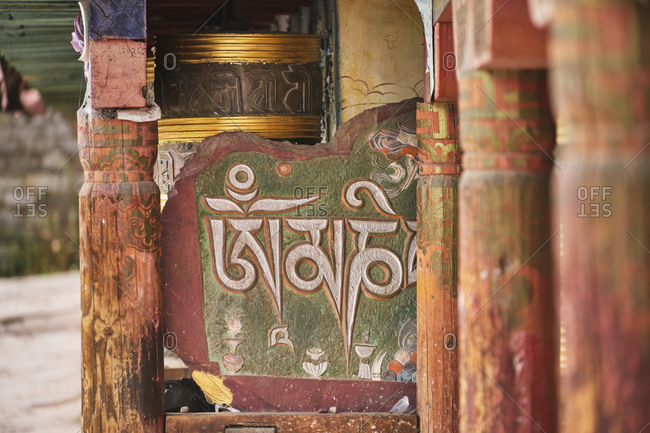 September 6, 2020: Weathered wooden columns with carved patterns and hieroglyphs placed near old antique temple