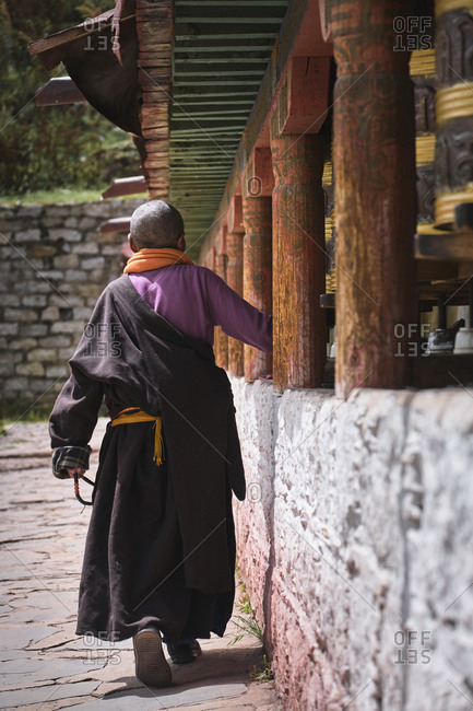 September 6, 2020: Back view of bald person in traditional colorful wearing near ancient oriental inscriptions