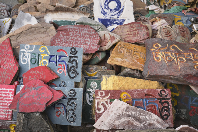 September 6, 2020: Overhead view of Sanskrit mantra Om Mani Padme Hum engraved on shabby surface of multi colored stone slabs in daylight