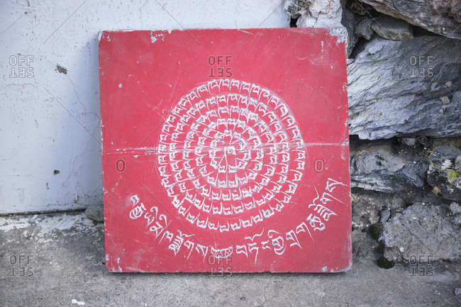 September 6, 2020: Mantra on old red square shabby stone slab on ground near pile of stones in yard of church