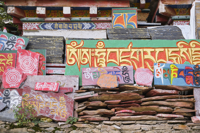 September 6, 2020: Sanskrit Mantra Om Mani Padme Hum on vibrant multi colored old shabby stone slabs in daylight
