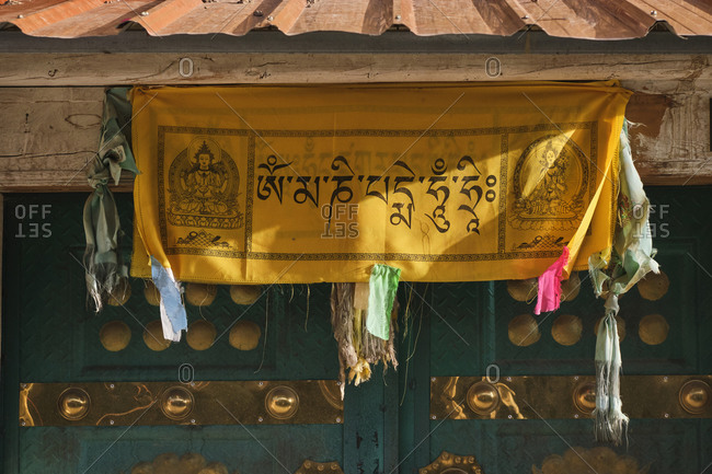 September 6, 2020: Vivid national pray with Tibetan symbols and Buddha on cloth with ribbons under roof