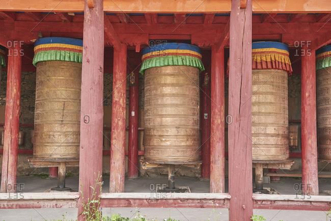 September 4, 2020: Old stone Tibetan rolls with sacred mantra consisting of sanskrit inscription near temple