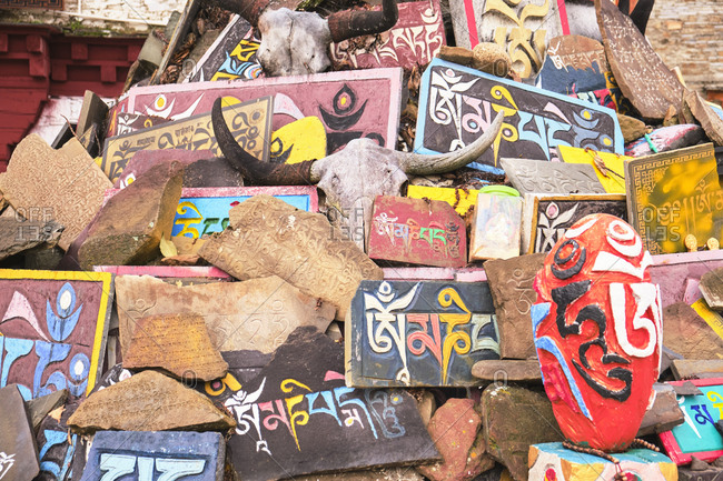 September 9, 2020: Pile of colorful concrete blocks with oriental inscriptions in Sanskrit in local area of small town