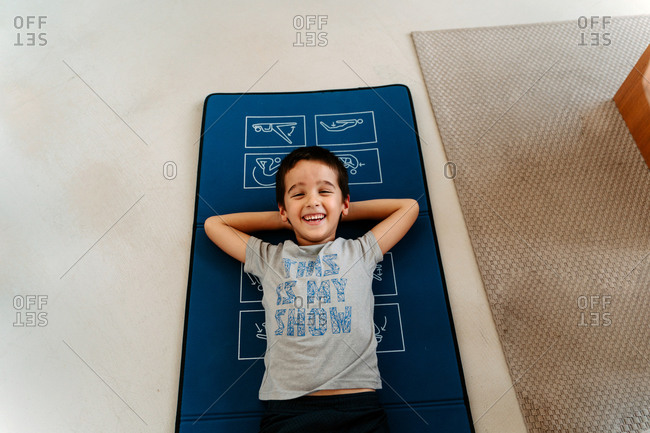High angle positive little boy in sportswear with hands behind head doing sit ups on yoga mat