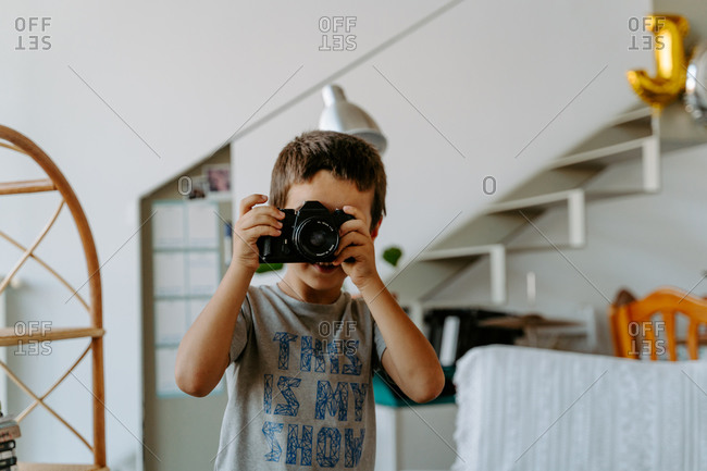 Content boy wearing casual shirt standing in modern apartment and shooting photo on professional photo camera