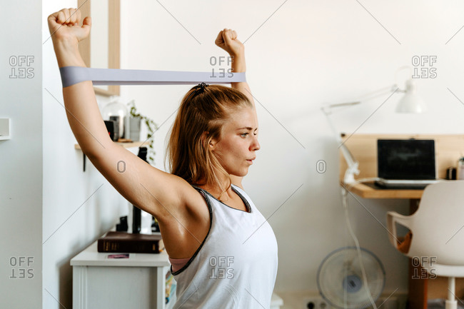 Sportswoman performing arms exercise with resistance bands working out at home