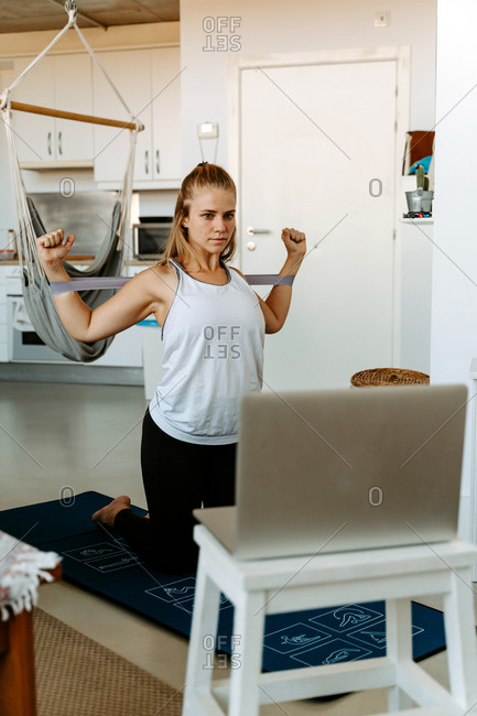 Sportswoman performing arms exercise with resistance bands while watching tutorials on laptop and working out at home