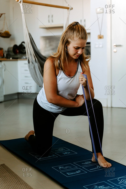 Full length young content sportswoman in activewear performing arms exercise by using elastic band while working out on mat at home