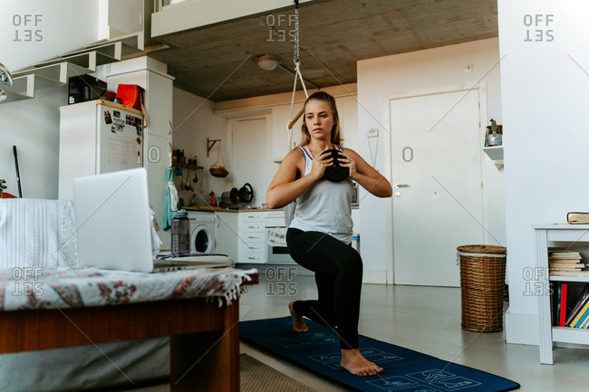 Concentrated young female in sportswear training with weight plate in kitchen at home watching tutorial on laptop