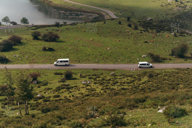 From above picturesque scenery of cars driving along narrow rural road running through lush verdant valley near tranquil lake