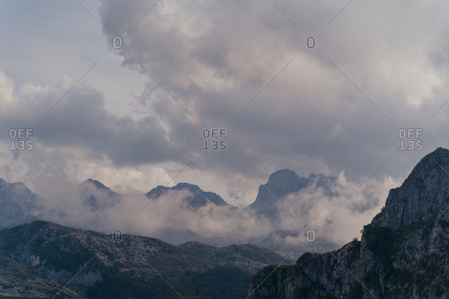 Scenic view of massive rocky mountain range with peaks in white heavy clouds located in peaceful highlands on overcast day