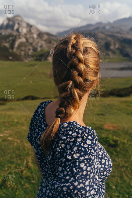 Back view of female in casual dress sitting on stone and enjoying magnificent views of majestic mountains and green valley surrounding peaceful pond