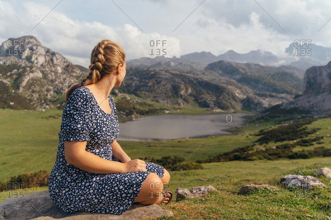 Side view full body female in casual dress sitting on stone and enjoying magnificent views of majestic mountains and green valley surrounding peaceful pond