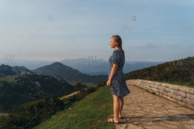 Side view full body young positive female impressed by amazing mountainous landscape standing on green hill and admiring views