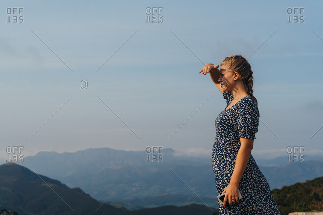 Side view positive young female with braid standing on hill and enjoying picturesque scenery of misty highlands