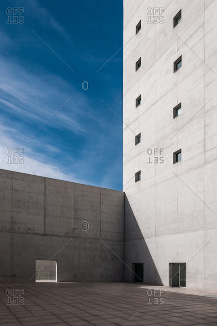 Facade of gray monolithic brutalist building with tiny windows and gate in tall concrete barrier