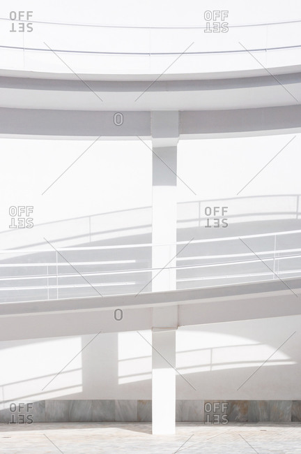 White smooth ramps or inclines with railings located outside modern futuristic building in sunlight