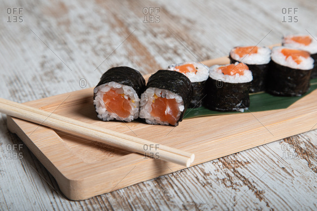 Set of Japanese hosomaki sushi rolls with fresh salmon fillet served on wooden board with chopsticks