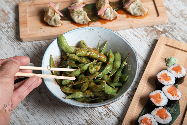 From above of bowl with edamame soy beans in pods served on wooden table with sushi rolls and boiled gyoza dumplings