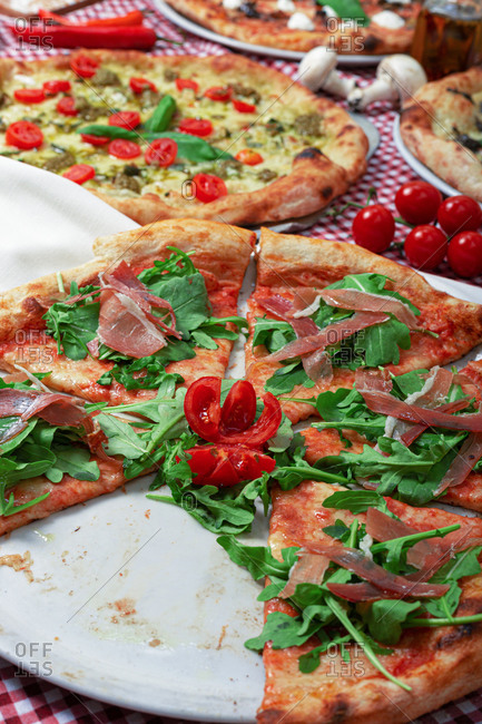 Appetizing sliced Italian pizza with Parma ham and fresh ruccola served on table with various types of pizza