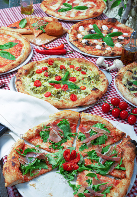From above of appetizing traditional Italian pizzas with various fillings served on table covered with checkered tablecloth during party
