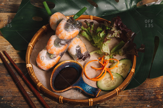 High angle composition of Vietnamese prawn rolls wrapped in rice paper and served on tray with barbecue sauce and lettuce leaves