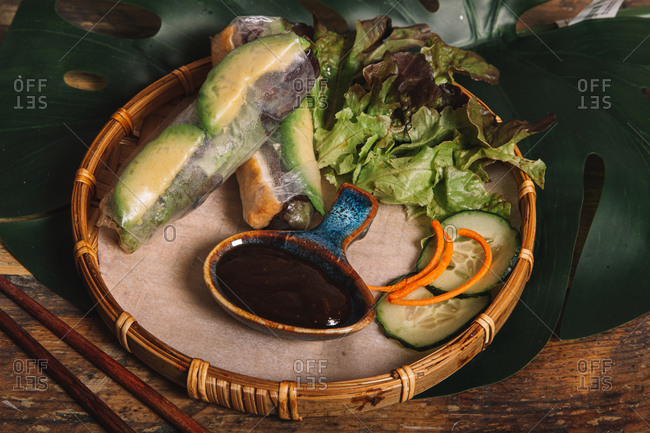From above composition of tasty Vietnamese rolls with avocado wrapped in rice paper and served on tray with barbecue sauce and lettuce leaves