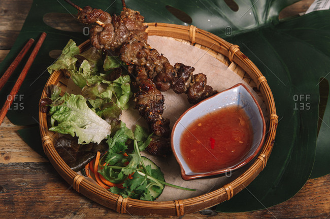 From above yummy grilled Vietnamese meat skewers served with spicy tomato sauce and lettuce on tray