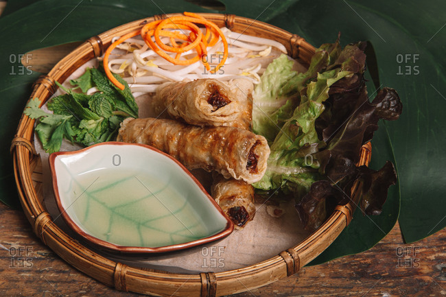 High angle of fried egg rolls served on plate with fresh lettuce and bean sprouts on wooden table in Vietnamese restaurant