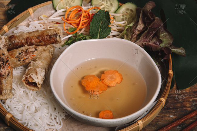 From above of traditional Vietnamese soup with carrots served on plate with nutritious egg rolls and rice noodles on table in restaurant
