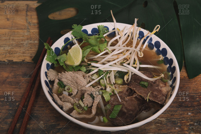 High angle of delicious Pho soup with beef and bean sprouts garnished with fresh parsley and green onions
