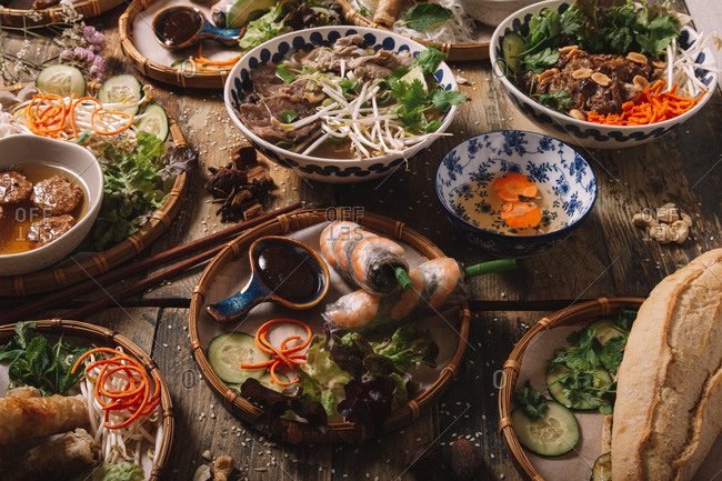 From above of assorted dishes of Vietnamese cuisine arranged on wooden table in luxury restaurant