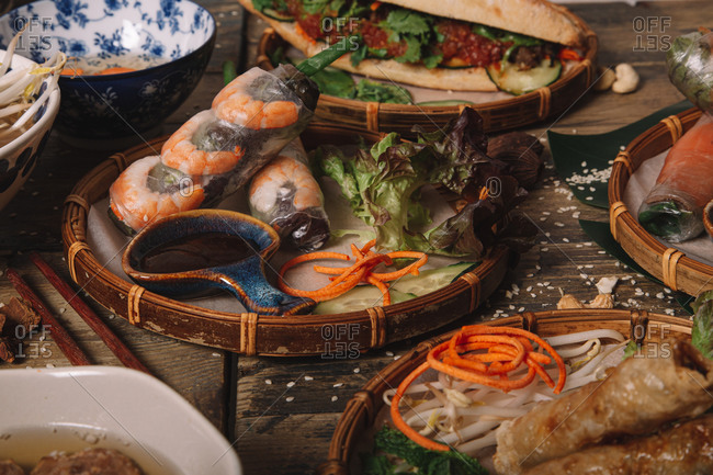 Appetizing Vietnamese spring rolls with shrimps served on table with various Asian food in traditional restaurant