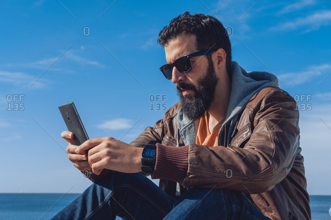 Low angle of concentrated young ethnic bearded man in trendy outfit and sunglasses browsing smartphone while resting on seashore against blue sky