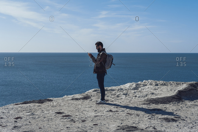 Side view of young bearded male traveler in stylish outfit and backpack using smartphone while standing on edge of rocky cliff in Seven Sisters on sunny day