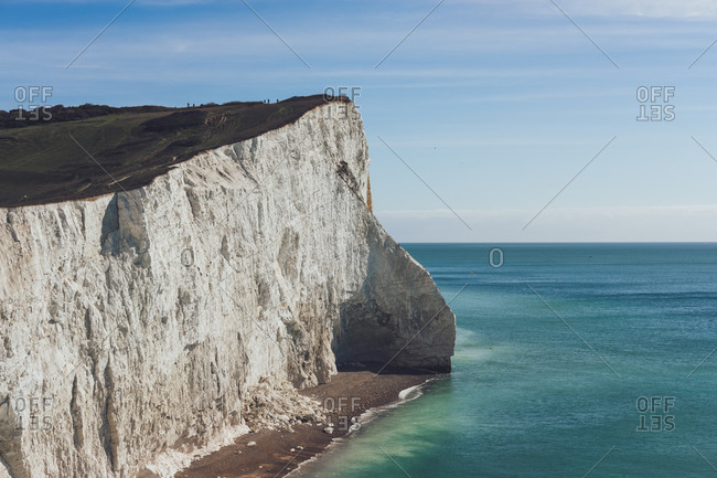 Picturesque scenery of huge chalk cliff covered with green grass located against blue sea on sunny day in Seven Sisters