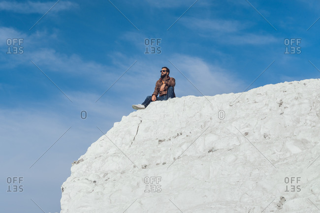 From below of unrecognizable male traveler in casual clothes sitting on edge of chalk cliff in Seven Sisters against blue sky
