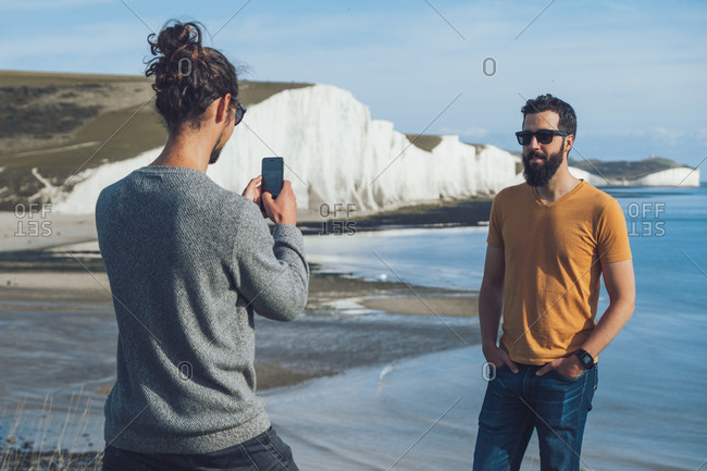 Back view of unrecognizable trendy guy taking photo of male bearded ethnic friend while spending holidays together in front of chalk cliff of Seven Sisters