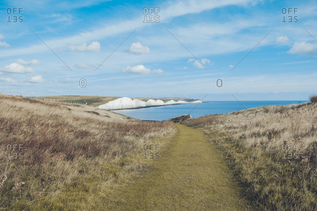 Amazing landscape of blue sea surrounded by chalk cliffs covered by grass in Seven Sisters on sunny day